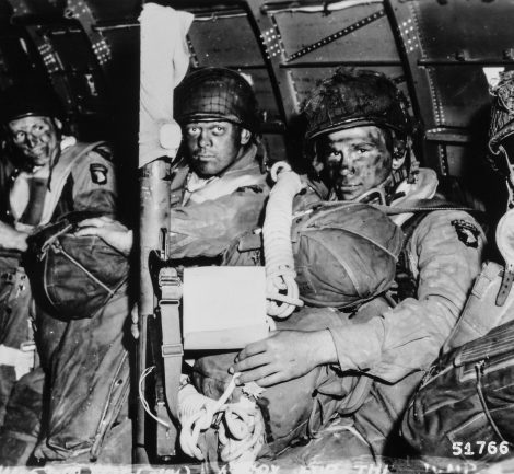 """ORIGINAL CAPTION: """"See You in Berlin. Resolute faces of paratroopers just before they took off for the initial assault ofD-Day. Paratrooper in foreground has just read Gen. Eisenhower's message of good luck and clasps his bazooka in determination. Note Eisenhower's D-Day order in hands of paratrooper in foreground."""" 1944"""