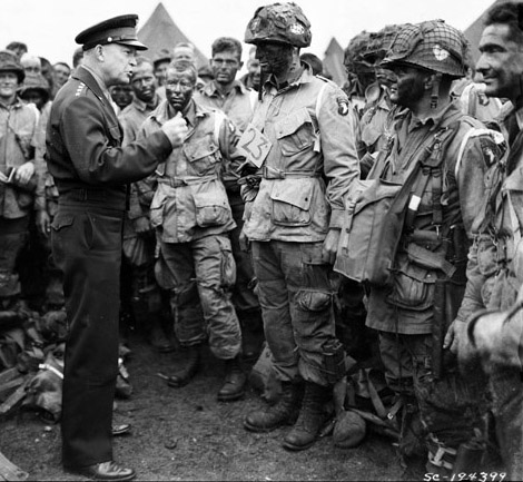 """General Dwight D. Eisenhower gives the order of the Day.  """"Full victory-nothing else"""" to paratroopers in England, just before they board their airplanes to participate in the first assault in the invasion of the continent of Europe.   06/06/1944 National Archives (NARA) Photo  RG 111-SC-194399 ARC: 531217  """"Access/Use Unrestricted"""" 111-SC-194399 03061_2006_001 (Note: soldier's uniform insignia scratched out in original negative) The USO is a not-for-profit organization and not part of the Department of Defense. The use of DoD imagery does not constitute an endorsement by DoD."""