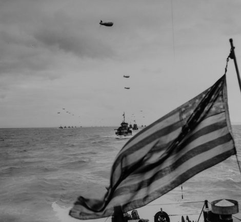 ORIGINAL CAPTION:  OLD GLORY MOVES TO NEW GLORY: Columns of Coast Guard LCI's, protected by barrage balloons against low flying Nazi strafers, advance upon the beaches of France in the wake of the Stars and Stripes. A Coast Guard combat photographer, going into the invasion on an LCI, caught this picture of the advance guard of the Liberation Fleet in the English Channel. 1944
