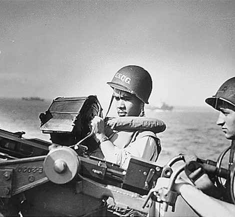"""""""Two Ohio Coast Guardsmen [John R. Smith, on the left, and Daniel J. Kaczorowski] stand at their gun aboard a Coast Guard-manned invasion transport on which they served during the invasion of Normandy."""" June 6, 1944"""